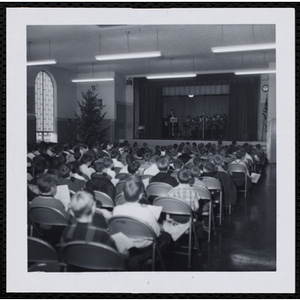 An audience of boys watches a boys' choir perform on stage