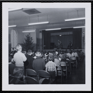 An audience of boys watch a clown on stage at a Christmas party