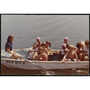 Children sit in a row boat with two adults
