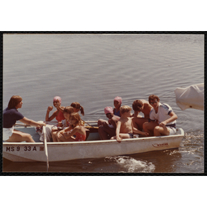Children ride in row boat with a woman and man