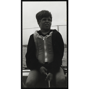A boy sits on the deck of sailboat on Boston Harbor