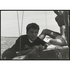 A boy hangs off the side of the sailboat as man looks on in Boston Harbor