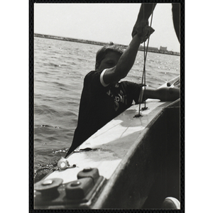 A boy grips the side of a sailboat as man holds him by his wrist in Boston Harbor