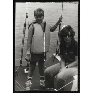 A boy stands next to a woman on the deck of a sailboat in Boston Harbor
