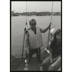 A boy stands next to a seated woman on the deck of sailboat in Boston Harbor