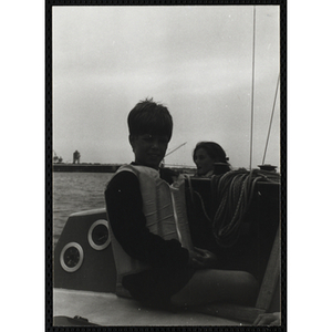 A boy sits on the deck of a sailboat in Boston Harbor