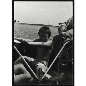 A boy sits on the deck of sailboat in Boston Harbor