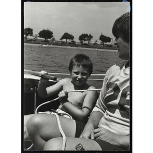 A boy and a teenage boy sit in a sailboat in Boston Harbor