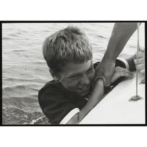 A boy hangs off the side of a sailboat as a man holds him by the arm in Boston Harbor