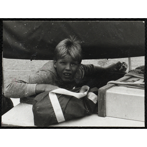 A boy rides on a sailboat in Boston Harbor