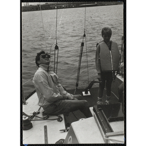 A boy stands next to a seated man on the deck of a sailboat in Boston Harbor