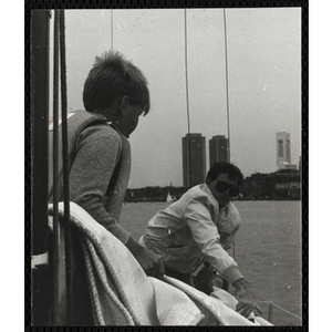 A boy and a man occupy a sailboat in Boston Harbor