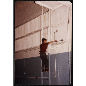 A boy reaches for a shelf on the wall of the Charlestown gymnasium