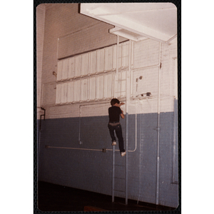 A boy climbs a ladder on the wall of the Charlestown gymnasium