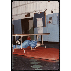 A boy crawls under a table at the Charlestown gymnasium