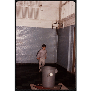 A boy stands behind a trash can at the Charlestown gymnasium