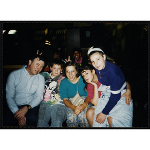 Site coordinator Liz Cinquino sits with three children and a man at the Tri-Club roller skating party at Chez Vous Roller Rink