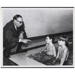 """""""Advertising Executive Kenneth D. Clapp (left) of Humphrey Browning MacDougall Inc., and South Boston Boys' Club swim team members, Michael Pyne and Joe Watts, talk about the clubs' recreational programs for inner city youth"""""""
