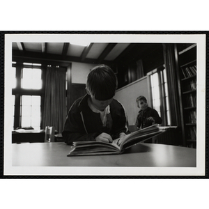A Boy reading a book at a table and another boy is standing in the background