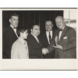 Arthur T. Burger, Executive Director of Boys' Clubs of Boston, holds a trophy and shakes hands with State Senator John E. Powers while others stand by during a Boys' Clubs of Boston awards event