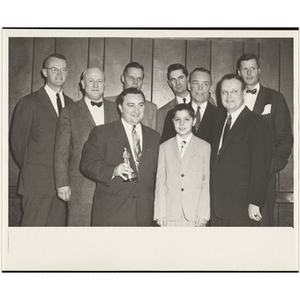 An award winner posing with several officers and guests, including State Senator John E. Powers, holding a trophy, at a Boys' Clubs of Boston awards event