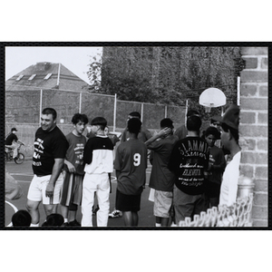 Players congregate courtside at a Chelsea Housing Authority Basketball League game