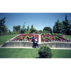 """Chinese Progressive Association member sits on a concrete-framed flower bed, where the flowers read """"I Am The Way"""""""