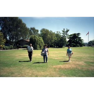 Chinese Progressive Association members walk across a grassy field in a Vancouver park