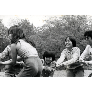 Children and young adults play tug-of-war