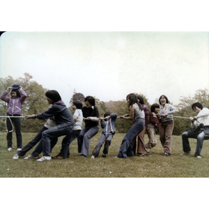 Children and young adults play tug-of-war in a field