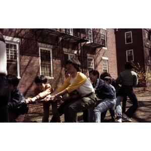 Boys and young men pull on a rope in a game of tug-of-war