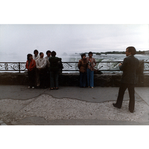 Chinese Progressive Association members gather together at Niagara Falls, with a man holding a camera nearby