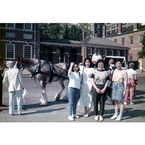Four women stand in front of a horse-drawn carriage at Philadelphia's Independence Hall