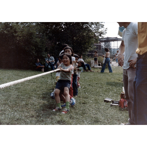 Children play tug-of-war in a grassy field, while two men watch on the side