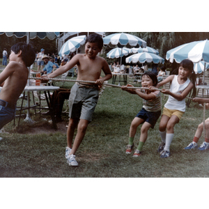 Children pull on a rope during a tug-of-war game in a grassy picnic area