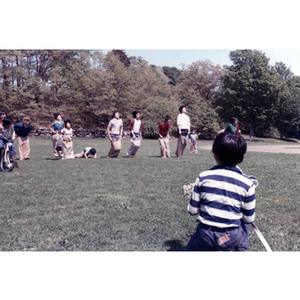 Association members compete in a sack race in a grassy field, while a young boy watches from the sideline