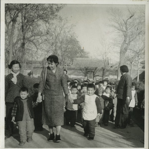 Shirley Graham Du Bois holding hands with two unidentified children