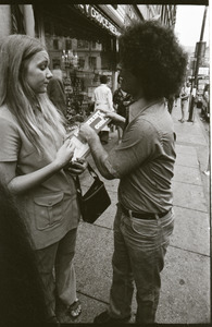 Abbie Hoffman walking in Harvard Square, talking with young woman (Church of the Final Judgment) handing out literature on the Second Coming