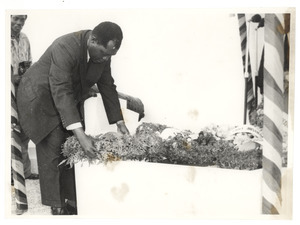Unidentified man lays a wreath at the graveside of W. E. B. Du Bois