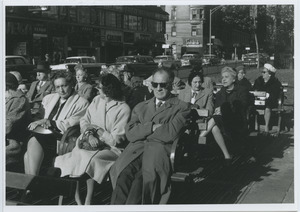People sitting on benches at the intersection of West 86th Street and Broadway in New York City