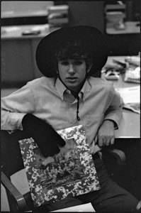 At the Boston University News Office: Peter Simon wearing hat and glove and holding copy of Rolling Stones', 'Their Satanic Majesties Request'