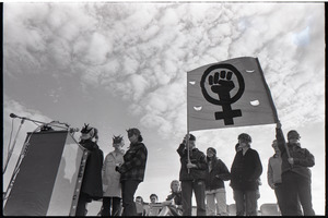 Anti-war rally at Soldier's Field, Harvard University: members of feminist group Bread and Roses wearing masks, speaking and holding a fist in a venus symbol
