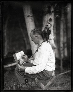 Arthur F. Clark sketching, with Cleo the monkey on his back