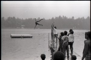 Group of summer campers (?) tossing a child into a lake, one onlooker wearing a Spirit in Flesh t-shirt
