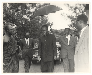 Unidentified man holds an umbrella over the head of Kwame Nkrumah at the state funeral of W. E. B. Du Bois