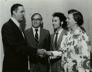 Randolph W. Bromery shaking hands with unidentified woman, while two unidentified men look on