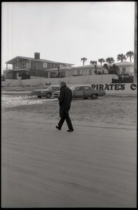 Middle-aged man walking along beach, beach homes in background