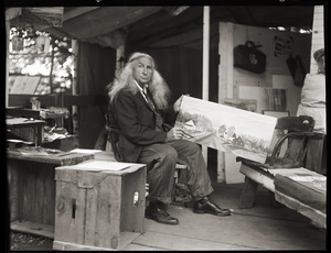 Albion L. Clough seated in his cabin, displaying a painting