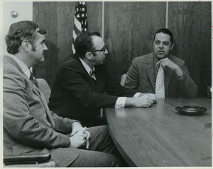Randolph W. Bromery sitting indoors conversing with two men