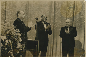 Paul Robeson clapping with two unidentified men
